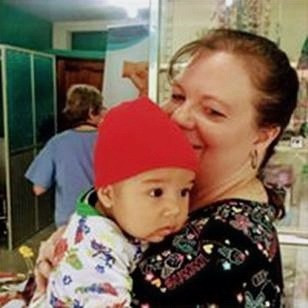 Cara Harrington, Executive Director of Just Jump Ministries, loves on a baby while his mom is examined