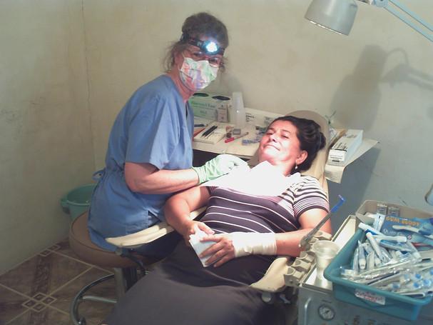 "Visiting USA hygientist Carol Deaner cleans teacher's teeth as part of ""Dental Awareness Week"""