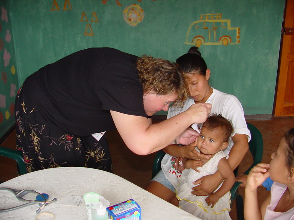 Medical mission NP Cheryl Lindgren examines this very cooporative young man's ear canal.