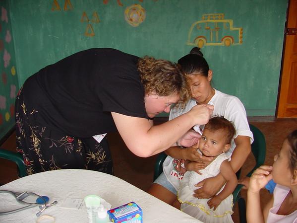 U.S. Nurse Practitioner Cheryl Lindgren examines toddler during 2002 medical mission