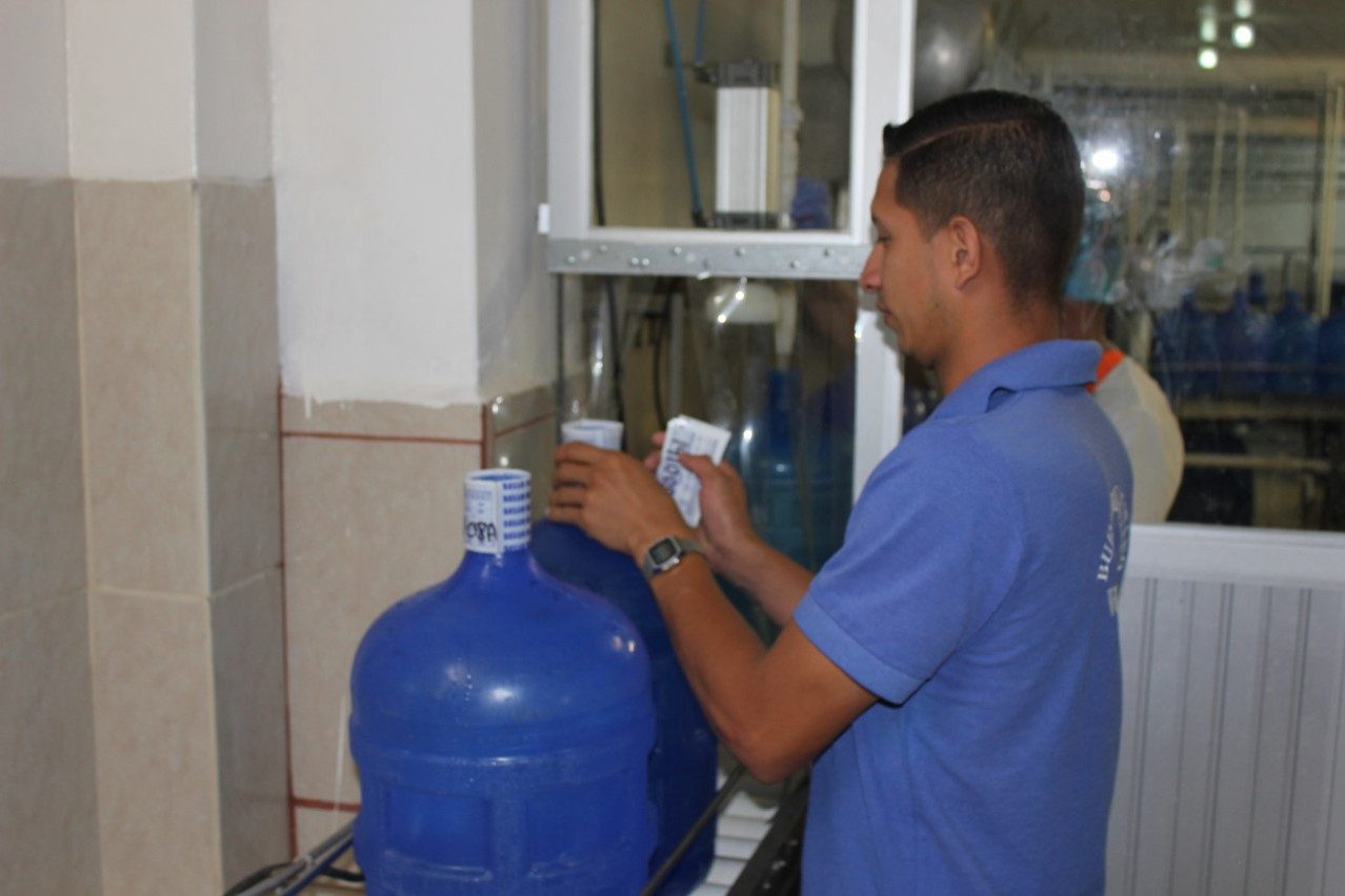 Jose putting seals over the bottle cap before pushing through electric sealer machine