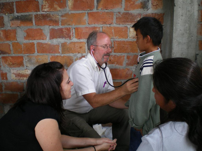 Medical Mission PA, Bill Simon rechecks for a heart murmur as Rebecca Egan translates for Mom
