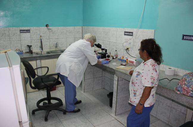 Buen Samaritano labor story. Medical mission NP,  Barbara Henderson takes advantage of microscope as Angelita observes