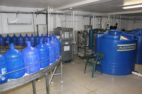 Washed bottles travel on rollers in a semi-circle to filling station