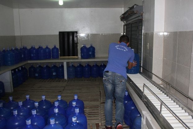 Jose pushing bottles on rollers to the front of the building.