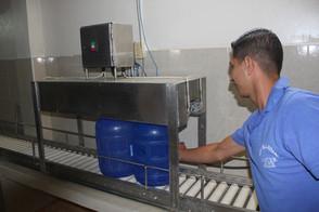 Jose pushing bottles through electric bottle cap sealer