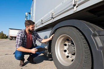 truck-driver-inspecting-tires-checking-d