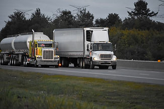 trailer-trucks-driving-road-surrounded-b