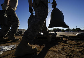 National Guard soldiers move sandbags fo