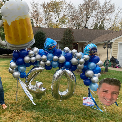 Organic balloons and giant beer mug with personalized age.