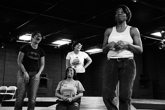 Black women laughing during play rehearsal, on a stage