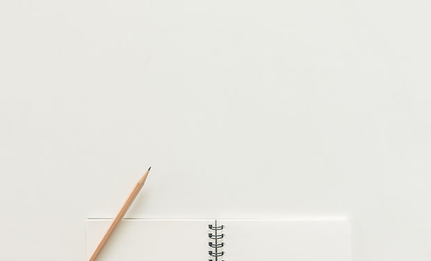 A white spiral bound notebook opened with a pencil