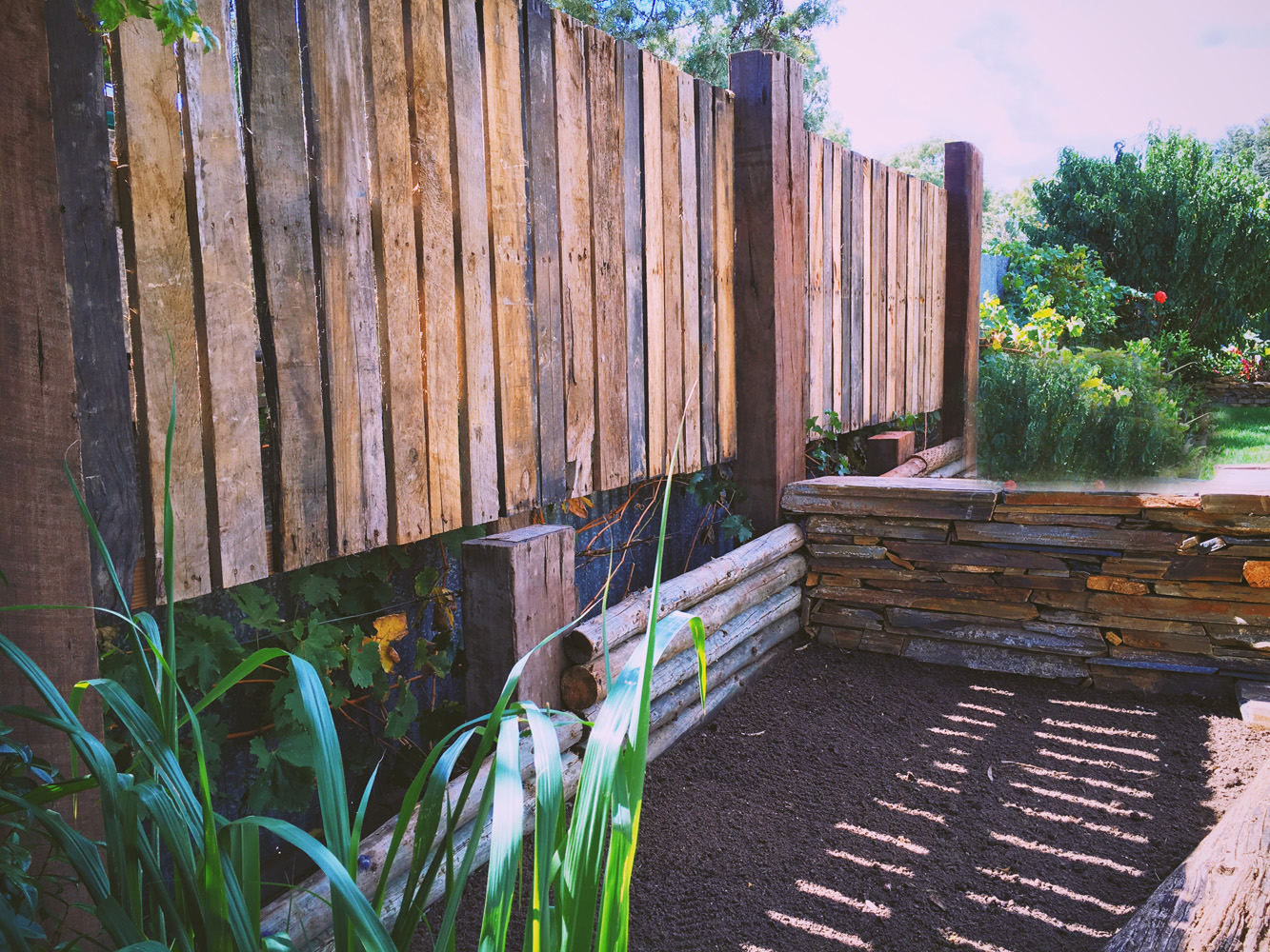 Recycled pallet fence with old railway sleepers