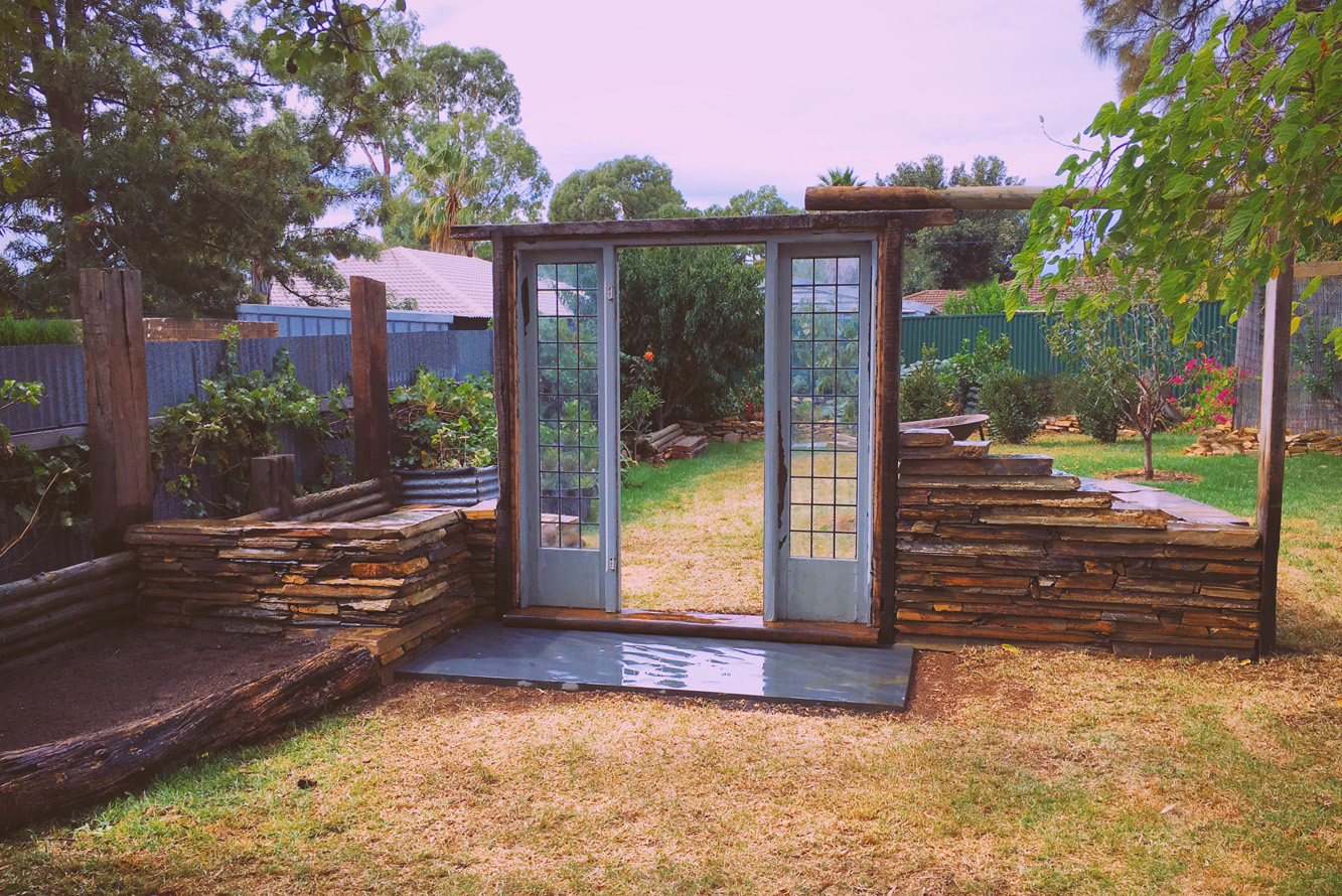 Old door built into a backyard to give the impression of a ruin