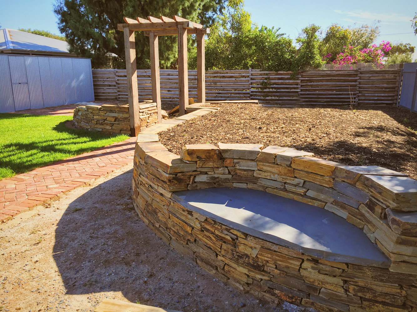 Elegant seat built into drystone wall with arbor behind
