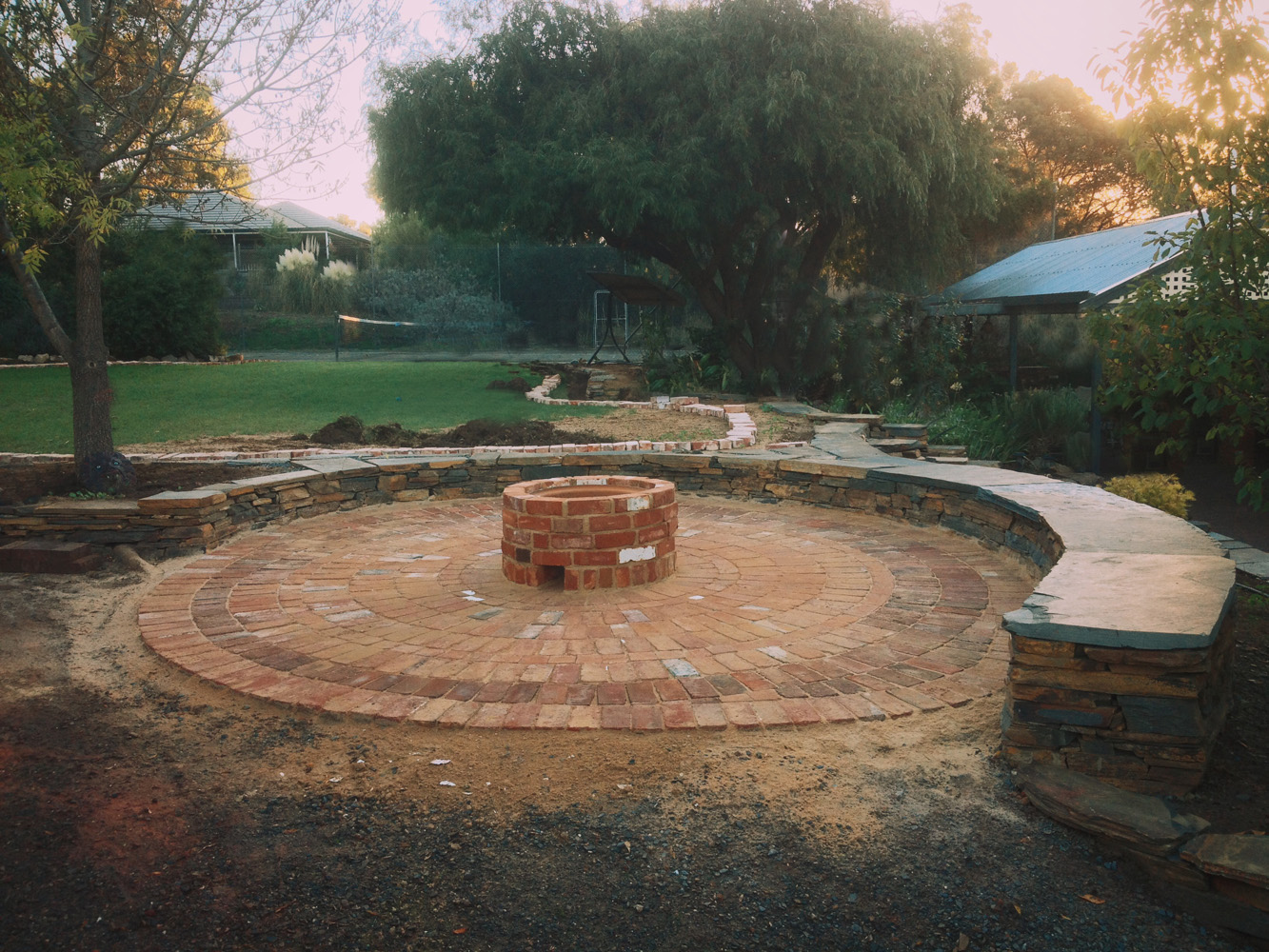 Stone seating, circular paving and a firepit