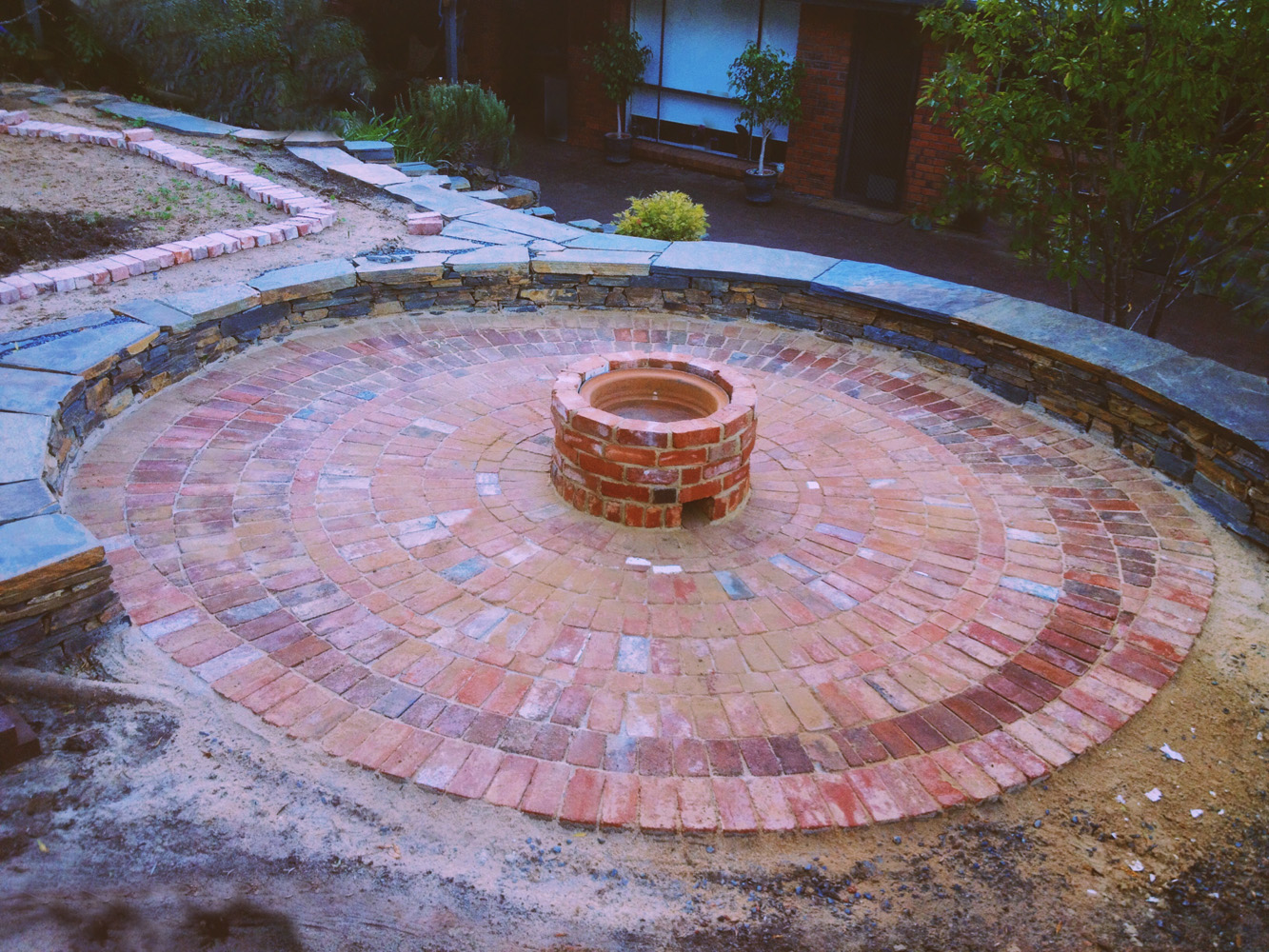 Stone seating, circular paving, and a firepit