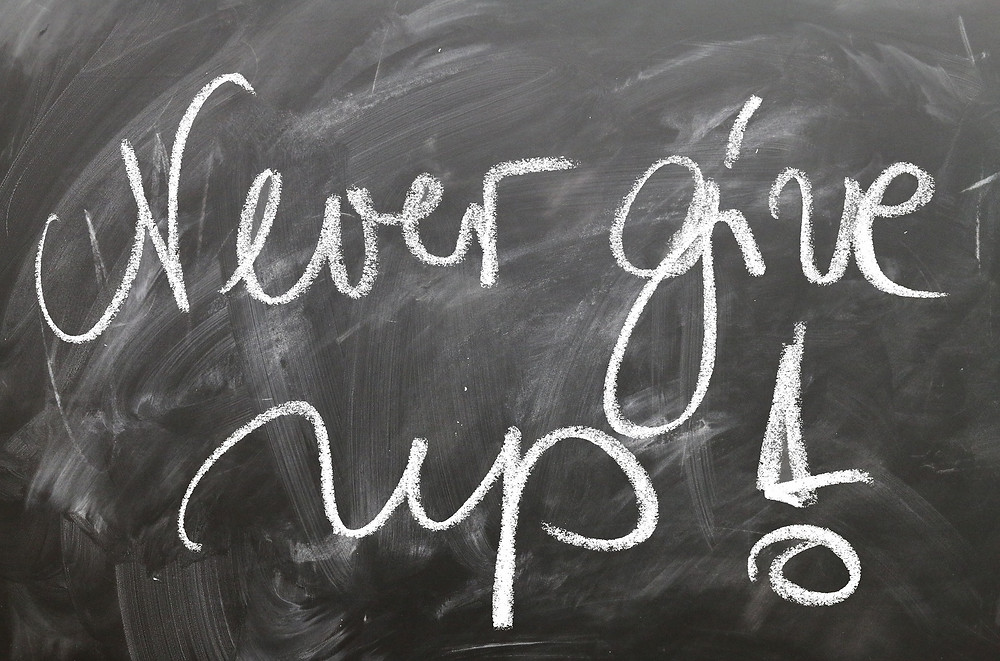 A Blackboard that reads: Never Give Up!