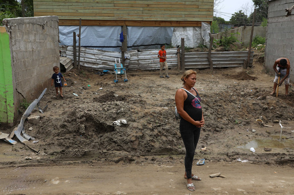 Chamelecón, San Pedro Sula, Honduras.   Brenda, her husband Franklin. and children in an empty space where their home used to be.