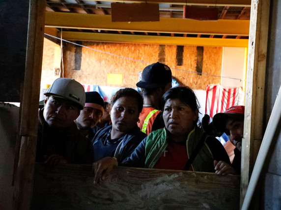 At a shelter provided by a local resident, migrants that decided not to move on to the new shelter gather looking for any donations that may have been brought in that morning.