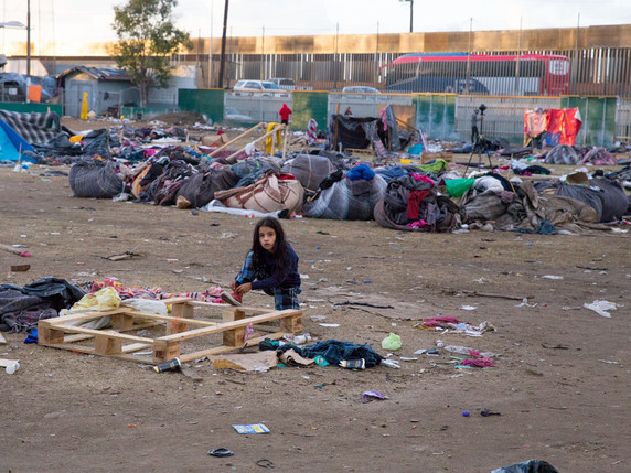 A migrant child ties her shoe in the middle of the empty Benito Juarez sports arena.