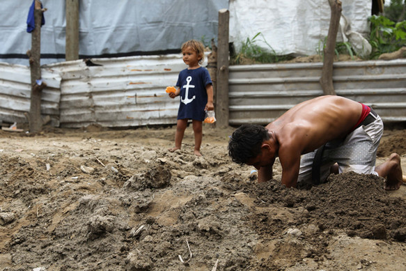 Chamalecón, San Pedro Sula, Honduras    Brenda's husband, Franklin, digs through the mud to begin the construction of a potential new home for his family.