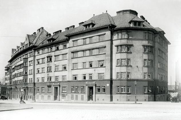 1920 ist der erste Bauabschnitt des Metzleinstaler-Hofs fertiggestellt. Mit seinem Bau werden neue Standards für den sozialen Wohnbau gesetzt: ein Vorraum in jeder Wohnung, direktes Licht in allen Wohnräumen, ein eigener Wasseranschluss sowie die Errichtung von für den Gemeindebau typischen Gemeinschaftsräumen, etwa eines Kindergartens.   Verglichen mit späteren Gemeindebauten des Roten Wien fällt auf, dass hier die Stiegeneingänge noch von der Straße aus zu betreten sind. Das geht auf seine ersten Entwürfe als Zinshaus zurück.  Foto: Metzleintaler-Hof um 1920, Bezirksmuseum Margareten