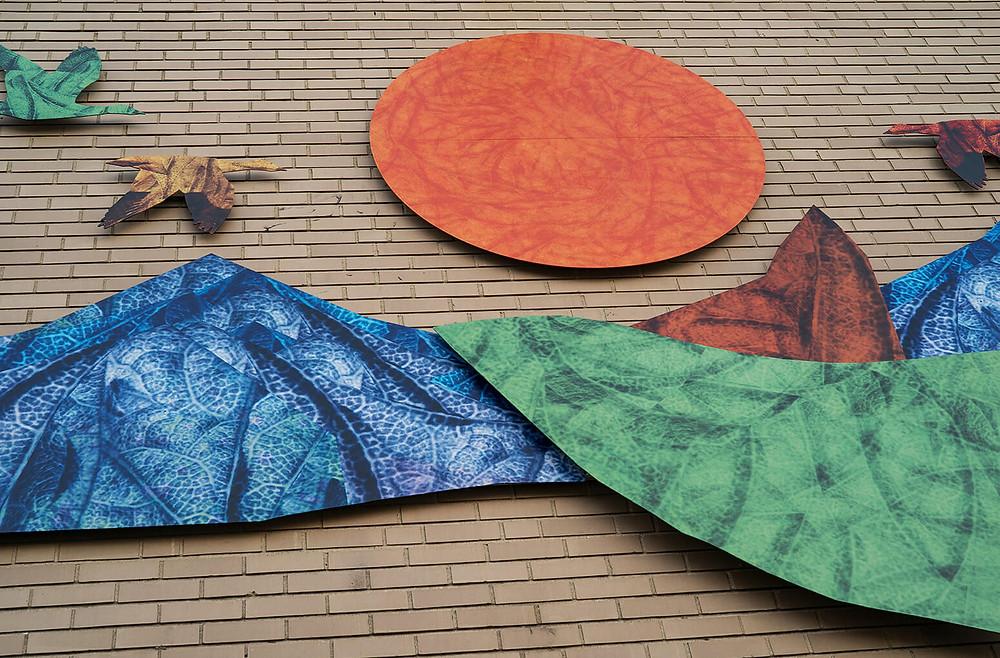 Mural of sun, birds and mountains on school facade.