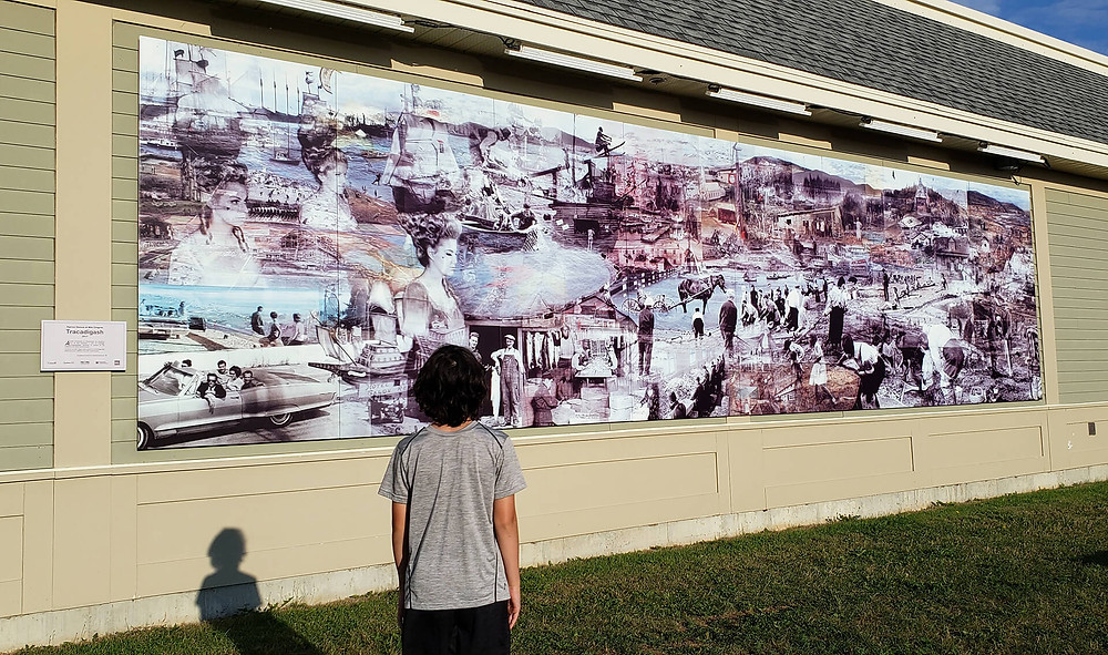 Mural with photo collage of women, ships, cars and town history.