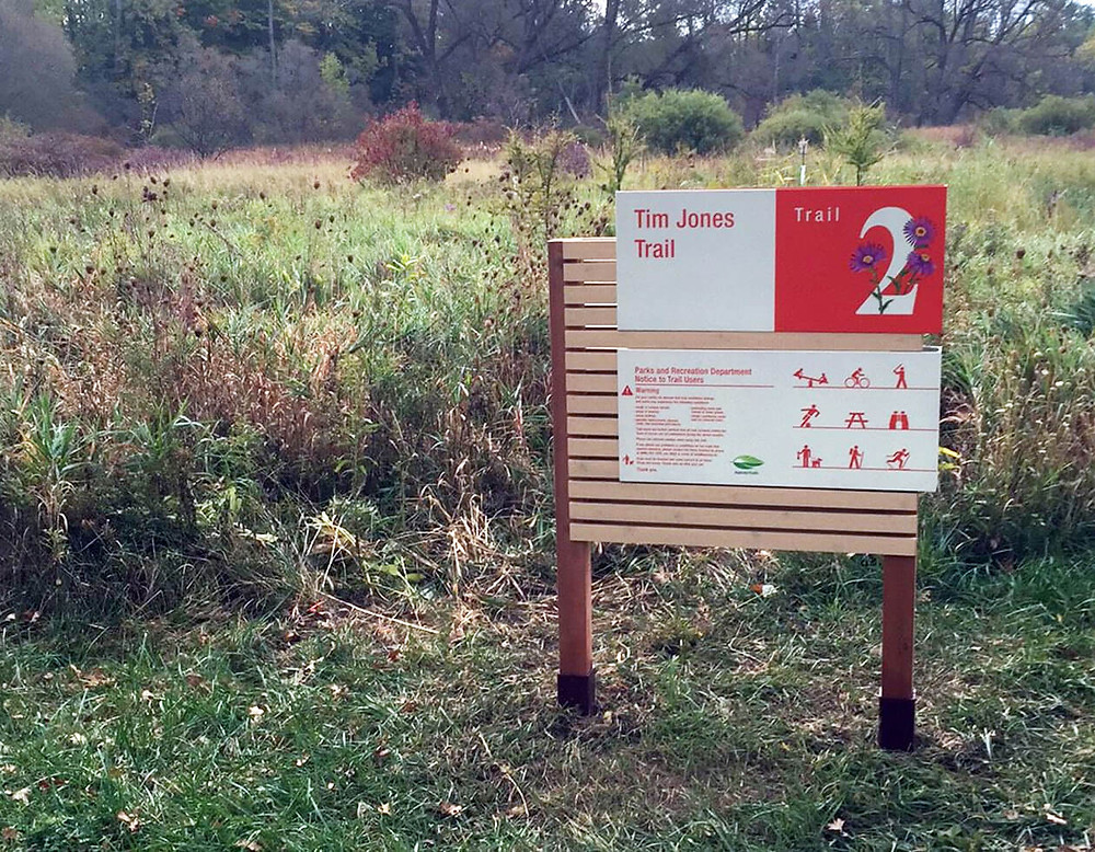 powder-coated graphics on aluminum sign in red and white on forest trail