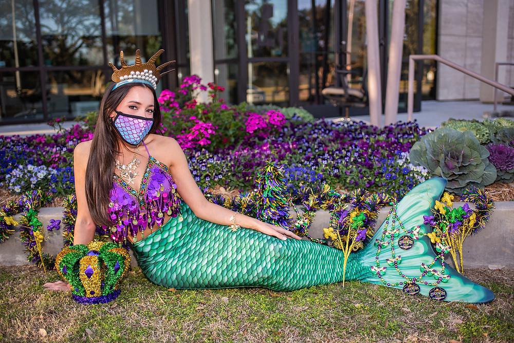 Mermaid posing with Mardi Gras beads