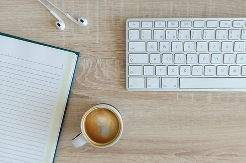 White computer keyboard with a notebook, headphones and a coffee