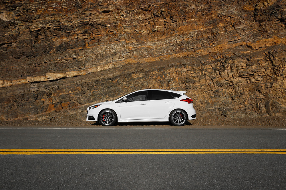 Side profile of a white Ford Focus ST against a canyon wall