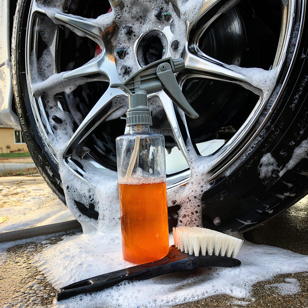soapy rims with brush and spray bottle with cleaning chemicals