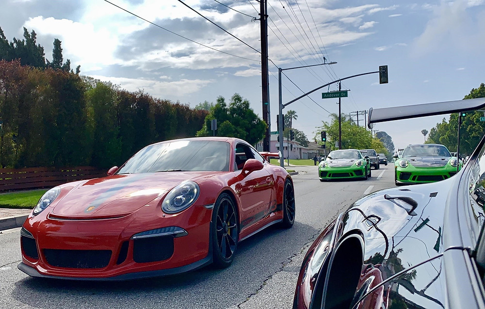 Front view of Red Porshe GT3 and Green Porshes
