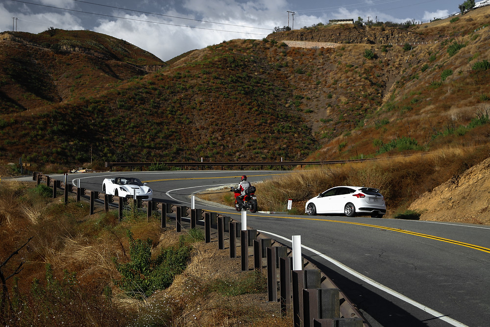 White C7 Corvette, White Ford Focus ST, and Red Motor Cycle Rider on windy mountain road - ditch standards