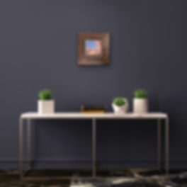 sunset painting above white table with plants