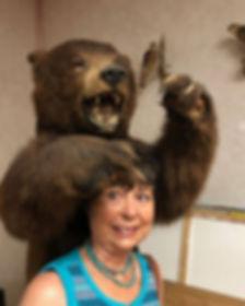 Stuffed bear grabs the head of artist Lindy Cook Severns during an art exhibit