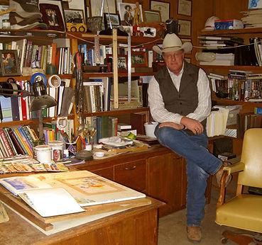 artist tim oliver in cowboy hat sitting on desk