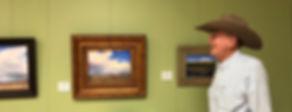 Jim Severns in cowboy hat admires paintings at exhibit