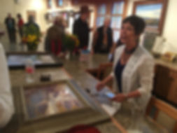artist lindy cook severns with framed painting and clients at gallery counter