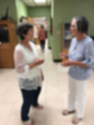 artist Lindy Severns with guest at art exhibit