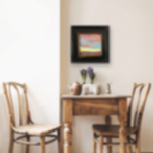 framed sunset painting above table and chairs