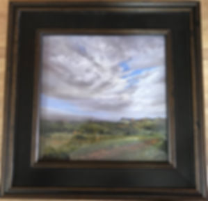dark frame on landscape painting of clouds over summer pasture