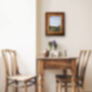 gold framed landscape painting above table and chairs