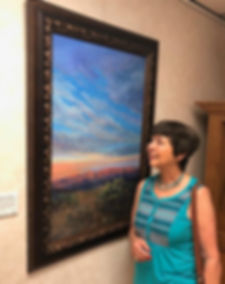 Texas artist Lindy Cook Severns looks at her large oil painting of a desert sunset