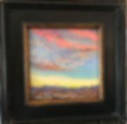 colorful desert sunset painting in dark wood frame