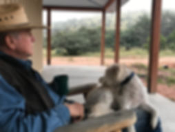 man jim severns in cowboy hat with white terrier and coffee cup on gallery porch