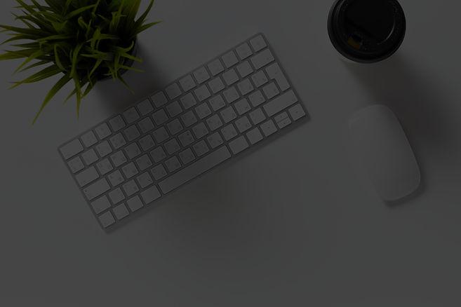 mesa com teclado, um vaso e uma chicara de café