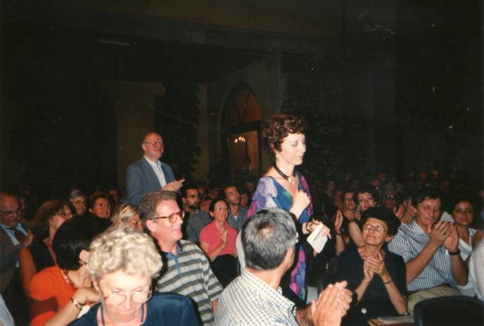 Maura in mezzo al pubblico nel cortile di Casa Manzoni per una serata di lettura delle sue poesie.